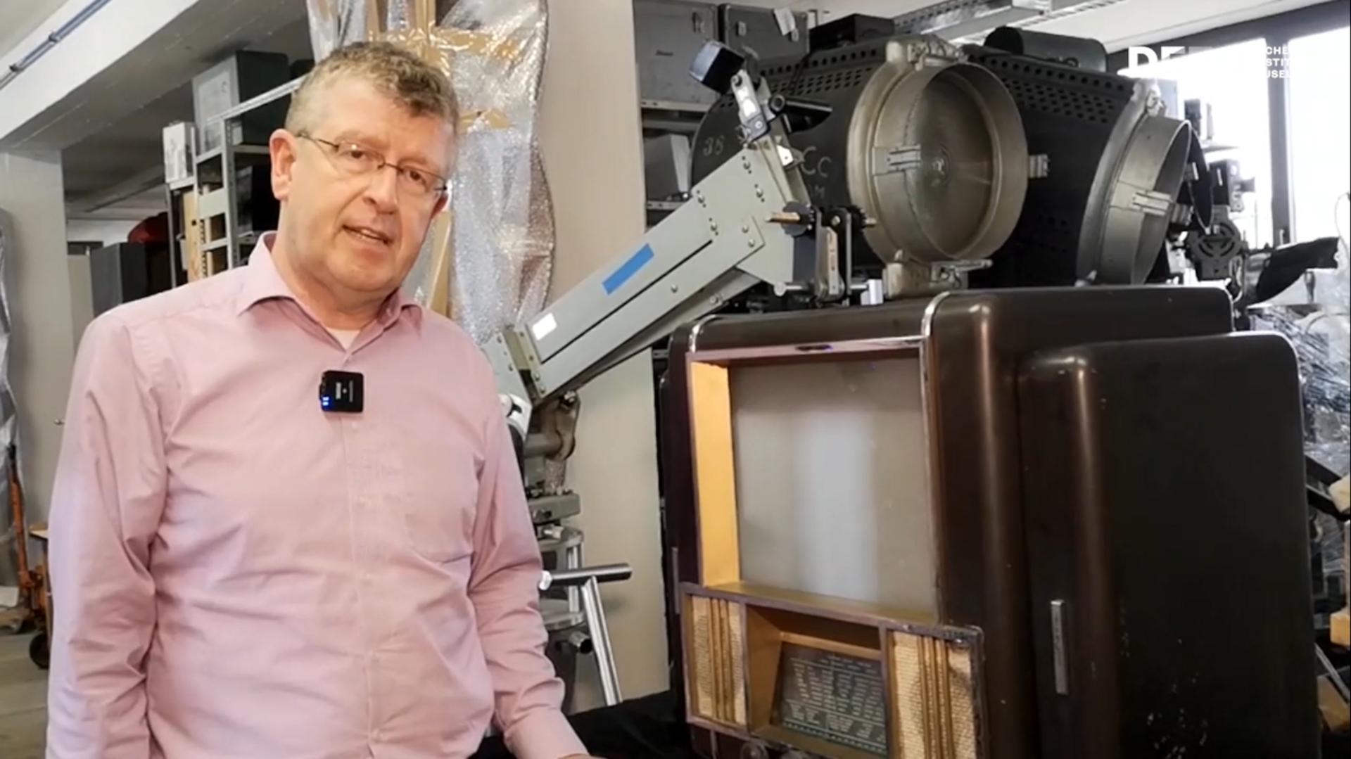 Der Leiter des Gerätearchiv des DFF Thomas Worschech im Gerätearchiv vor einem Projektor